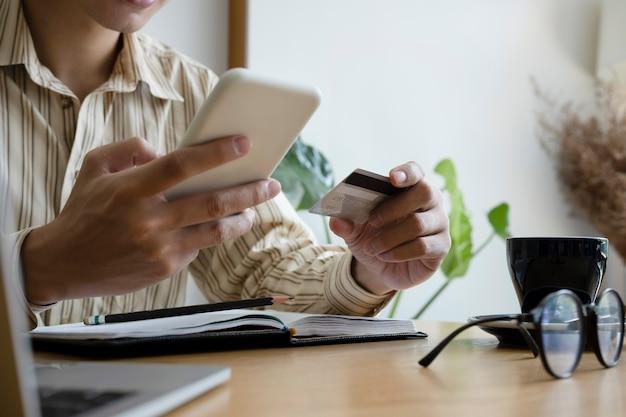 Обрезанный снимок молодой человек, держащий кредитную карту и использующий мобильный телефон для онлайн-банкинга.