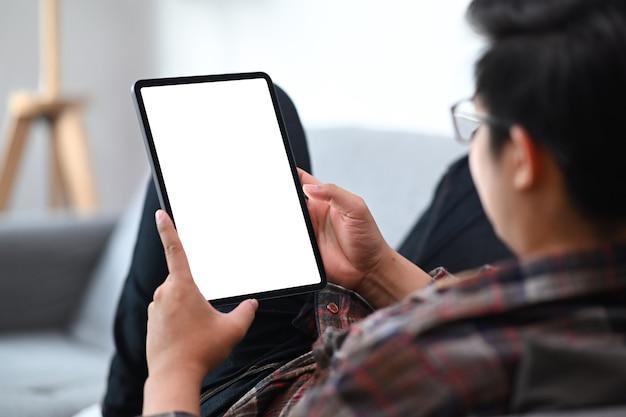 소파에 앉아서 디지털 태블릿으로 뉴스를 읽는 젊은 남자가 잘립니다.