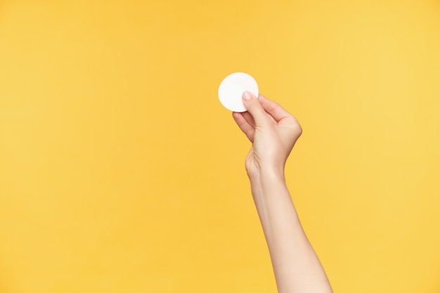 Cropped shot of young pretty woman's hand holding white cotton pad with fingers while being isolated over orange background. human hands and beauty concept