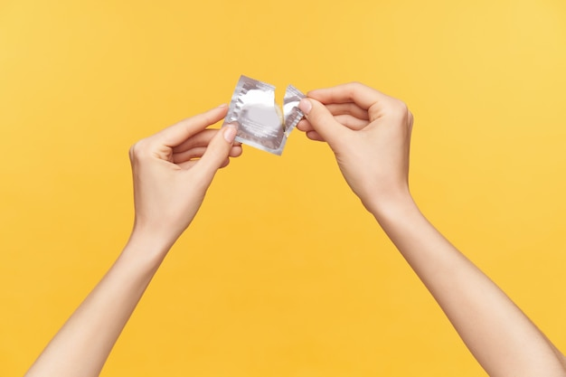 Cropped shot of young raised female's hands keeping silver pack with condom and unpacking it while being isolated over orange background. relations and sex concept