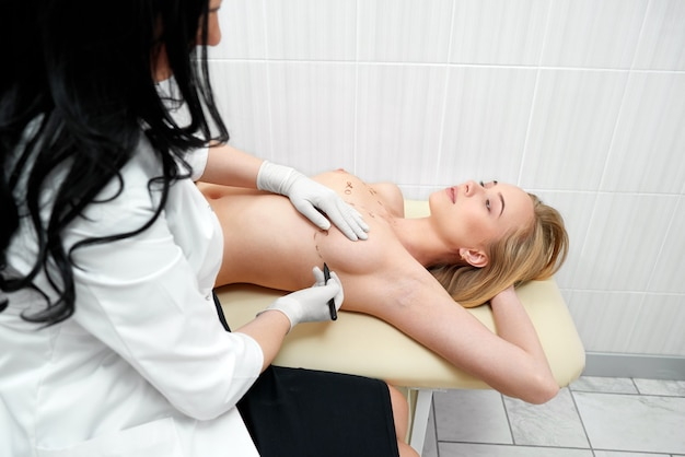 Cropped shot of a young woman getting her breast examined by doctor at the hospital gynecology mammalogy plastic surgery augmentation medical concept.