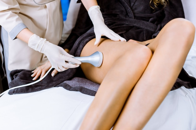 Cropped shot of young woman getting rf-lifting treatment of her legs by professional woman beautician.