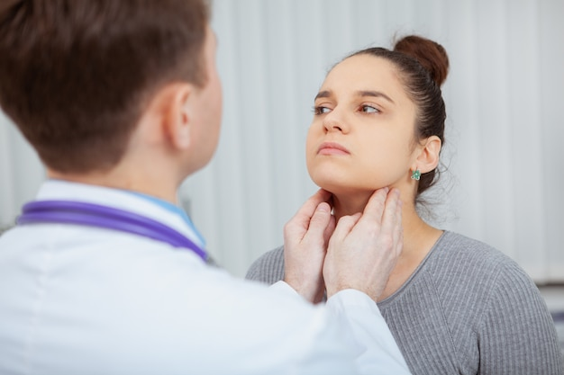 Cropped shot of a young women having her neck and throat examined by doctor at the hospital.