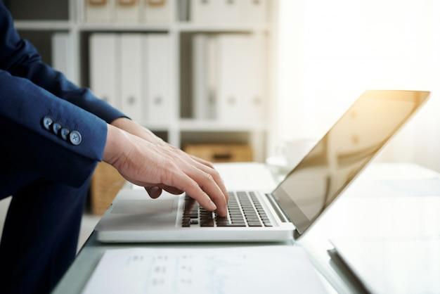 노트북에서 일하는 익명 사업가의 측면보기 자른