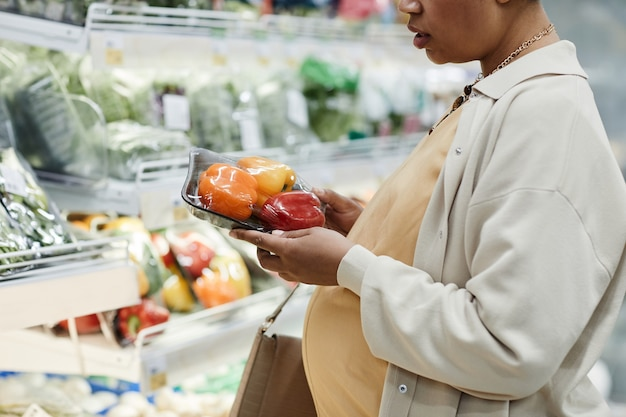 Обрезанный вид сбоку портрет беременной афро-американской женщины, покупающей продукты во время покупок в супермаркете