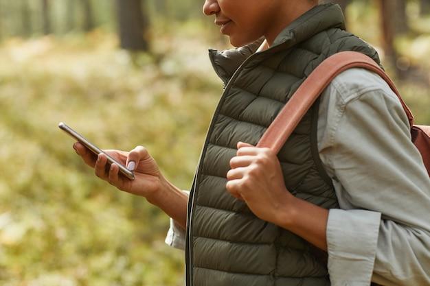 Обрезанный вид сбоку молодой афроамериканской женщины, использующей смартфон во время похода на переднем плане ...