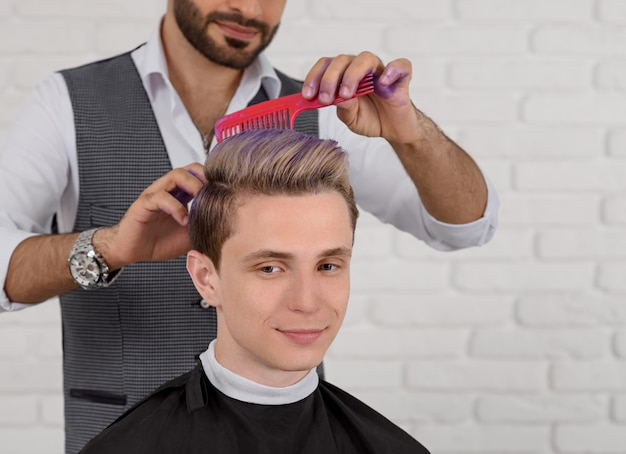 Cropped sideview of hairdresser doing hair violet colored toning for young boy.