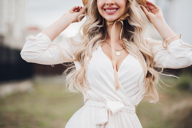 Cropped stock photo of a gorgeous blonde woman with long wavy hair wearing hat with bows and white dress. blurred background.