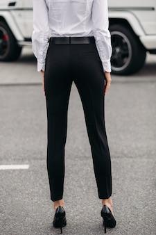 通りに立っている白いシャツとフォーマルな黒いストレートのズボンと黒い革のかかとで認識できない女性のトリミングされたストックフォト。ファッションモデル。ドレスコードのコンセプト。