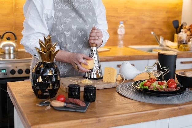 サラダのまな板にエプロン粉チーズの匿名の女性のクロップドストックフォト。木製のカウンターの黒いプレートにフレッシュトマト、レタス、ソーセージ。家庭での料理のコンセプト。