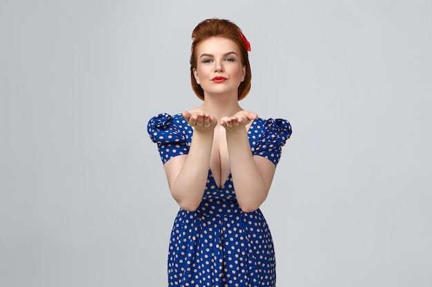 Cropped studio shot of attractive stylish young caucasian female wearing bright make up and retro blue dotted dress with low cut neck holding open palms and pouting lips, blowing air kisses
