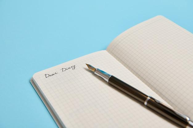 Dear diary라는 단어가 있는 열린 메모장의 자른 스튜디오 샷과 텍스트 복사 공간이 있는 파란색 배경에 격리된 잉크 펜