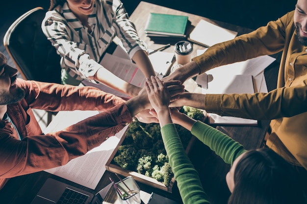 책상 위에 손을 모으는 캐주얼 정장을 입고 네 명의 쾌활한 전문 기업인의 높은 각도보기 위의 자른 상단