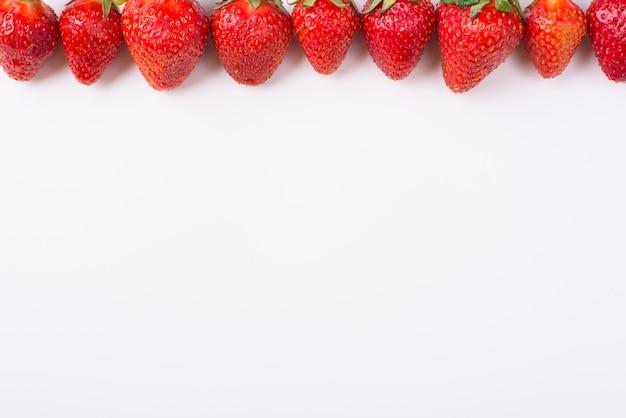 白い背景の上から上から並んでいるイチゴの俯瞰写真の上のクロップドトップ