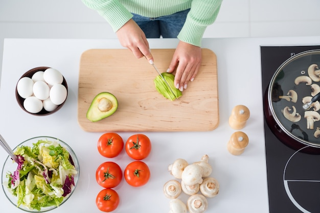 Cropped top above high angle view portrait of girl hands cutting avocado