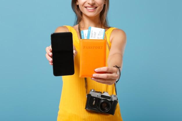 Обрезанный путешественник турист женщина в желтой одежде держит камеру мобильного телефона билеты на синем