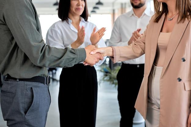 同僚と現代のオフィスで握手している2人の白人ビジネスマンを切り取った。フォーマルウェアの男性と女性。パートナーシップとコミュニケーションの概念。スペースをコピーします。成功した仕事、コワーキング。