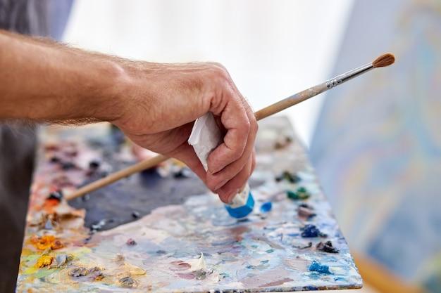 切り取られた認識できないアーティストがチューブから絵の具を絞り出し、絵の具を混ぜて描画します