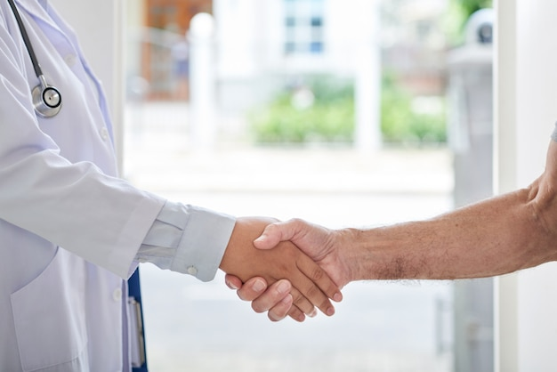 Cropped unrecognizable doctor and patient shaking hands