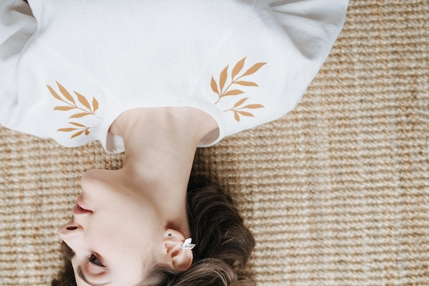Cropped upside image of a beautiful young woman in summer dress with leaf pattern lying on the floor inside a room. pretty brunette with short hair indoors.