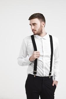 Immagine verticale ritagliata del dipendente maschio caucasico giovane alla moda bello con barba rifilata e taglio di capelli alla moda che posa alla parete dello studio, distogliendo lo sguardo, tenendo la mano sulle sue bretelle nere