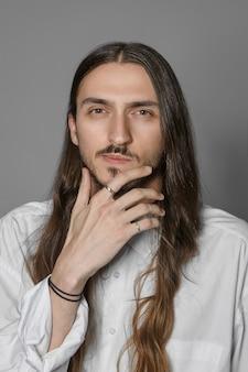 スタイリッシュなアクセサリーと白いシャツを着て、何かを考えながらあごをこすり、不確かな表情をしている、長い髪の思いやりのある物思いにふける若いひげを生やした男のトリミングされた垂直方向のビュー