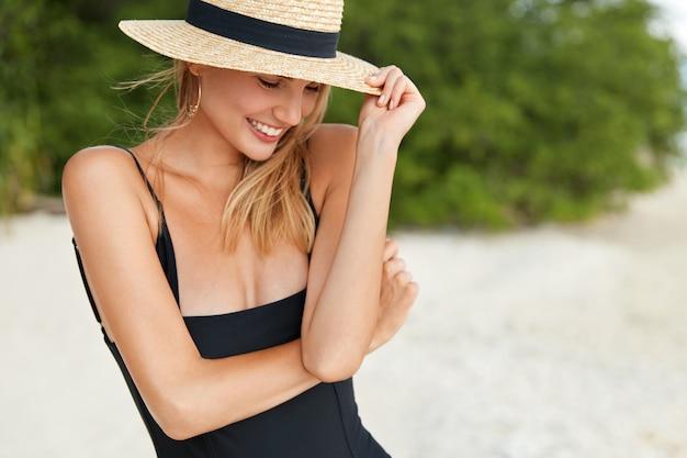Vista ritagliata di adorabile giovane donna indossa costume da bagno e cappello estivo, guarda positivamente verso il basso, ha una passeggiata all'aperto sulla spiaggia sabbiosa vicino alla vegetazione verde. la femmina carina rilassata ha ricreazione all'oceano