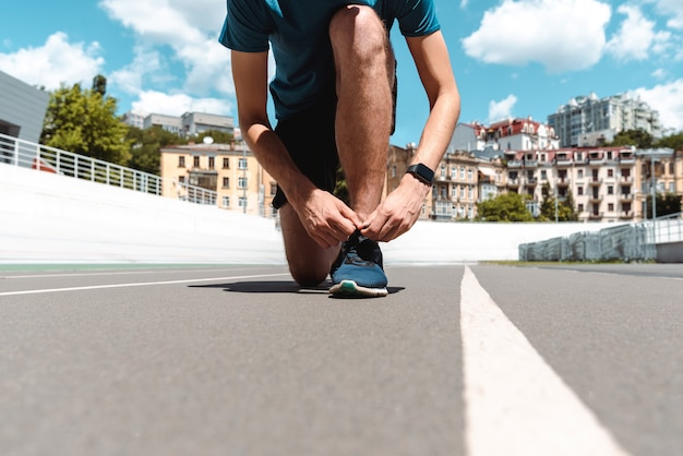 Cropped view of athletic young sportsman in smartwatch touching sneakers on running track with buildings