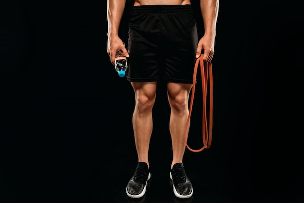 Cropped view of bodybuilder with elastic band and water isolated on black