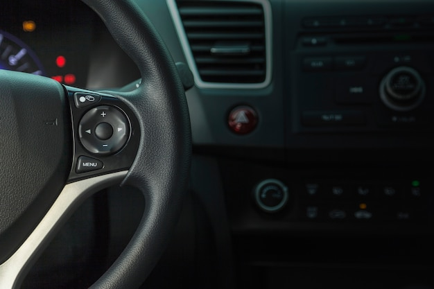 Cropped view of car inside driver place, interior of prestige modern car, steering wheel