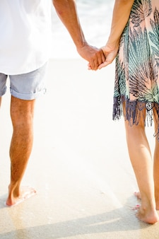 Cropped view of couple holding hands on beach