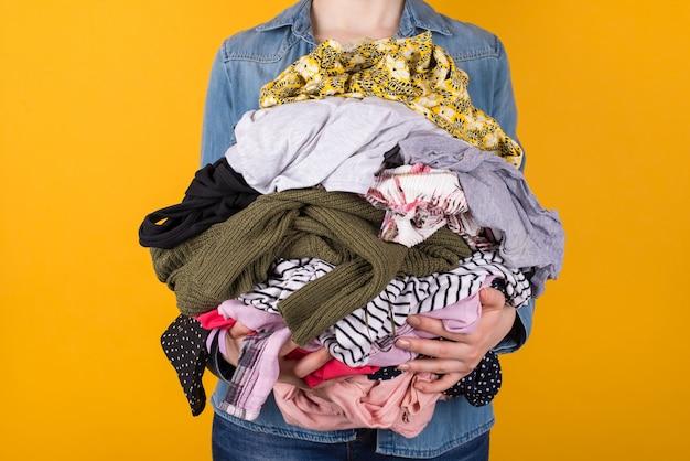 黄色の背景に分離されたさまざまな服をたくさん持っている女性のトリミングされたビューのトリミングされた写真。洗濯のコンセプトをやっています。中古のコンセプトを何を着るか