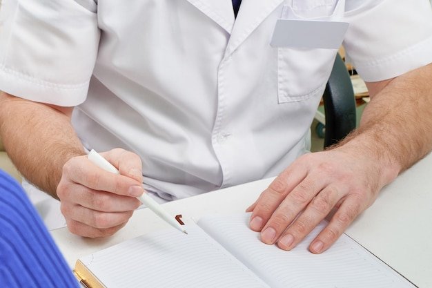 Cropped view of doctor writing in notepad during consulting a patient