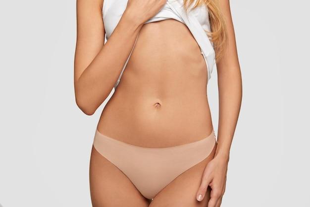 Cropped view of fit woman shows her belly, has slim body