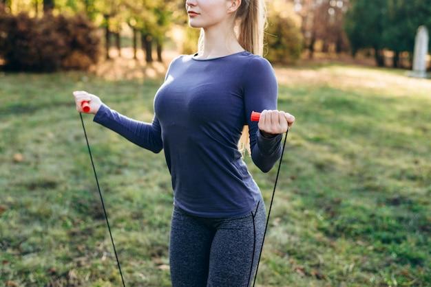 トリミングビュー、公園の女の子は彼女の手に縄跳びを保持しています。