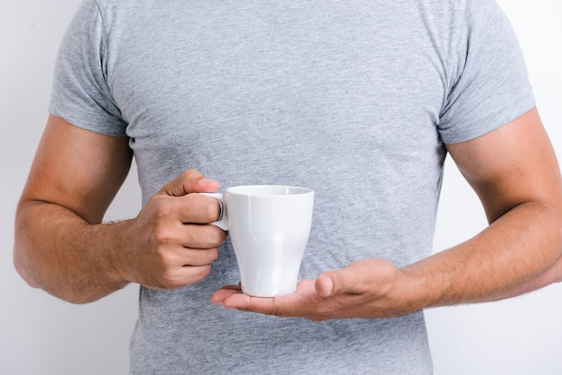 Cropped view of the handsome man standing and holding a cup of morning tea or coffee while posing at the camera. stock photo