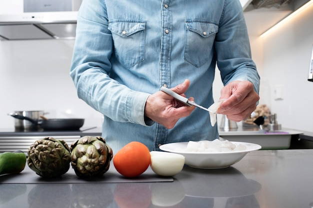 Cropped view of male cutting vegetables on chopping board at kitchen