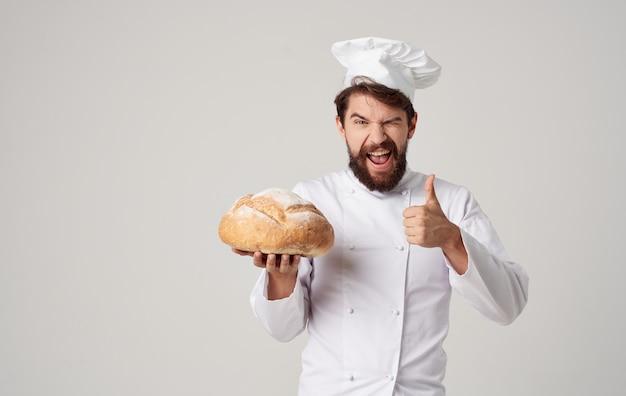 Обрезанный вид профессионального шеф-повара с приготовленной буханкой хлеба в руке на светлой стене Premium Фотографии