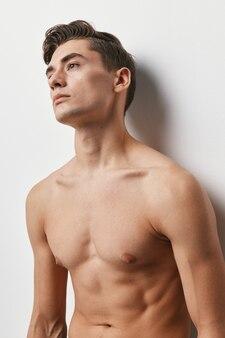 빛에 벌거 벗은 몸통을 가진 섹시한 남자의 자른보기