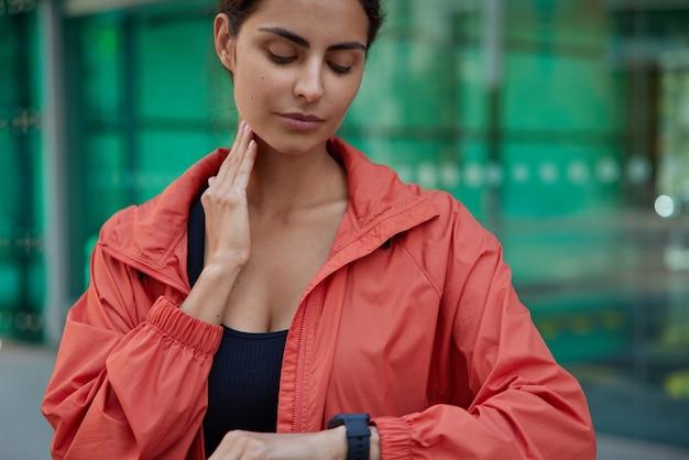 훈련 후 목에 맥박을 확인하는 노락을 입은 활동적인 스포츠 여성의 잘린 보기는 녹색 흐릿한 현대 스마트워치 포즈를 보고 있습니다