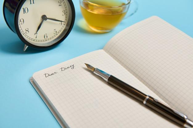 Dear diary, 알람 시계, 복사 공간이 있는 파란색 배경의 찻잔 옆에 있는 잉크 펜이 있는 열린 메모장의 잘린 보기