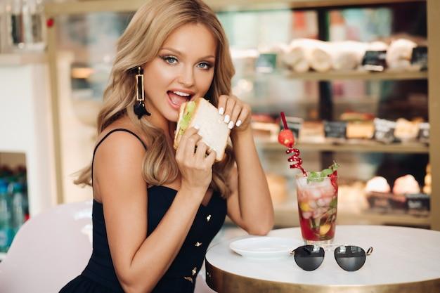 카메라를 보고 카페에서 맛있는 샌드위치를 먹는 매력적인 여성의 모습. 점심 시간에 맛있는 패스트푸드를 즐기는 메이크업과 헤어스타일을 한 배고픈 금발. 아침 식사와 음식의 개념입니다.