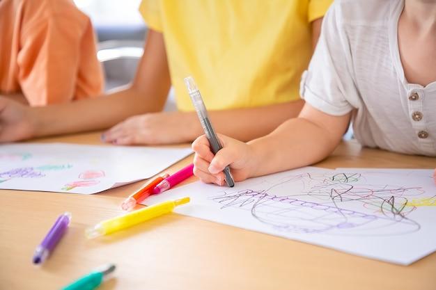 펜으로 종이에 그림 어린이의 자른보기. 인식 할 수없는 세 아이가 테이블에 앉아 낙서를 그립니다. 선택적 초점. 어린 시절, 창의력 및 주말 개념
