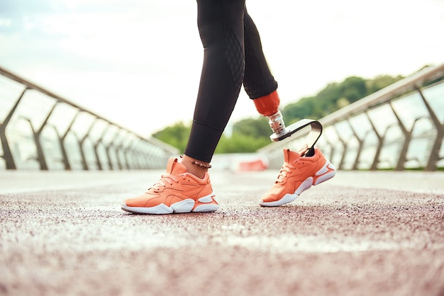 Обрезанный вид женщины-инвалида с протезом ноги, стоящей на мосту утром