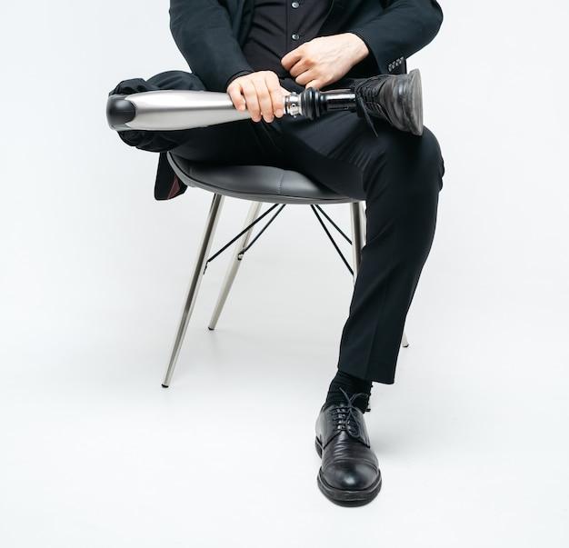 Обрезанный вид инвалидов молодого человека с протезом ноги, сидя на стуле, концепция протеза