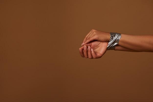 어두운 베이지색 배경에 덕트 테이프로 묶인 여성 손의 자른 보기. 침략, 불평등 및 여성에 대한 폭력 제거를 위한 국제의 날을 위한 사회적 개념. 복사 공간