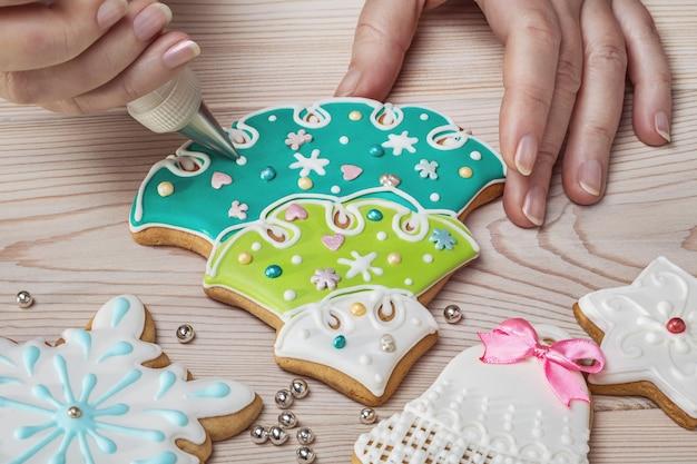 Обрезанный вид женских рук с домашними рождественскими пряниками с глазурью на деревянном столе.