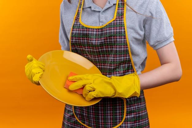 Обрезанный вид девушки в фартуке и резиновых перчатках, моющей тарелку с помощью губки