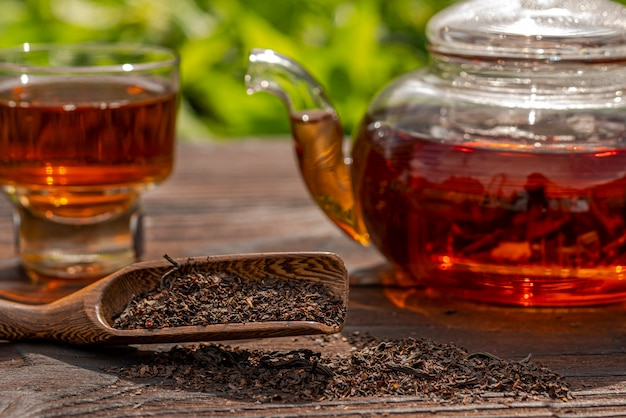 Обрезанный вид стеклянного парового чайника, элегантная чашка, бамбуковая ложка и чайный деревянный столик
