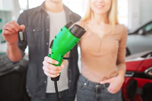 緑の充電プラグのビューを手に、電気自動車のコンセプト。
